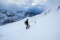 Winter climber ascending steep snow covered slopes towards summit of Hustind, Flakstadøy, Lofoten Islands, Norway