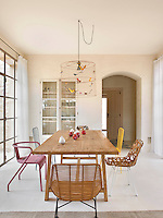 The dining area at one end of the open-plan living space is furnished with a large wooden table and a collection of mis-matched designer chairs