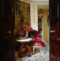 Double mahogany doors open into the stone tiled floor of a small circular entrance hall