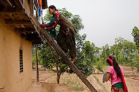 Nisha Darlami, 19, goes upstairs to her mother's bedroom as her mother carries her 1 month old baby girl, Bushpa, in Kalyan Village, Surkhet district, Western Nepal, on 30th June 2012. Nisha eloped with her step nephew when she was 13 but the couple used contraceptives for the next 6 years to delay pregnancy until she turned 18. In Surkhet, StC partners with Safer Society, a local NGO which advocates for child rights and against child marriage. Photo by Suzanne Lee for Save The Children UK