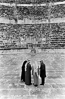 Jordan. Amman. Downtown. Town center. Antique roman open-air theatre. Three men and a woman, all jordanian, visit the ancien monument. The woman is wearing a black abaya on her body and her head as part of muslim tradition and religion. 15.02.02 © 2002 Didier Ruef
