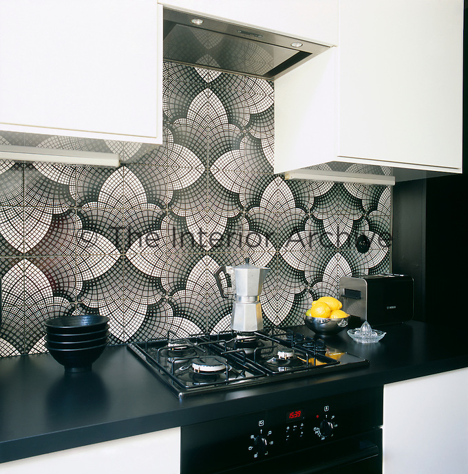 Graphic patterns, added to a simple palette of black and white create an elegant combination shown to great effect in this small kitchen