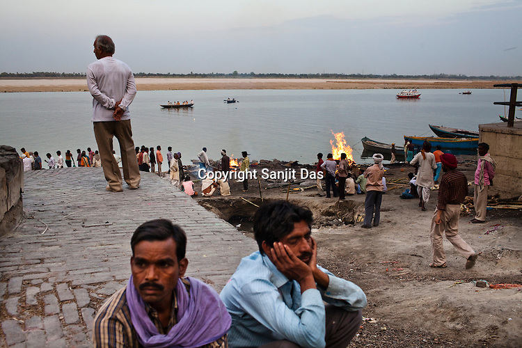 Mourners sit on the ghats while the dead body of their relative burns in the background at the Harishchandra Ghat in the ancient city of Varanasi in Uttar Pradesh, India. Photograph: Sanjit Das/Panos