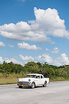 Cuba; a white, classic 1956 Buick car driving along the highway from Havana to Jucaro