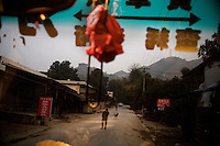 Seen through a bus windshield, a man and dog walk down a road in mountainous rural southern Yunnan Province, China, near the Vietnam border.