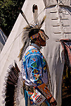 Profile of Native American wearing Northern Traditional Pow Wow Regalia and Tepee. <br />