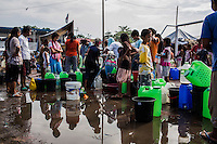 Survivors of the Zamboanga City rebel attack line up for water as they take refuge in the city's largest stadium in Zamboanga, Mindanao, The Philippines on November 4, 2013. These Internally Displaced People (IDP) had taken refuge in this stadium after surviving the 3 week long attack by MNLF rebels. Photo by Suzanne Lee for SPRINT-IPPF