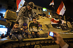 Egyptian soldiers pose for pictures with children in the Giza district of Cairo following news that Egyptian President Hosni Mubarak had stepped down February 11, 2011.  (Photo by Scott Nelson)