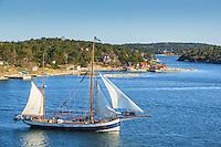 Tvåmastars segelskuta seglar förbi Korsholmen utanför Dalarö i Stockholms skärgård
