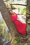 Thoughtful young woman sitting alone in the woods wearing a long red dress in summer