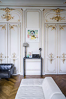 A contemporary console table occupies a space between a pair of Haussmann double doors embellished with gilt plasterwork