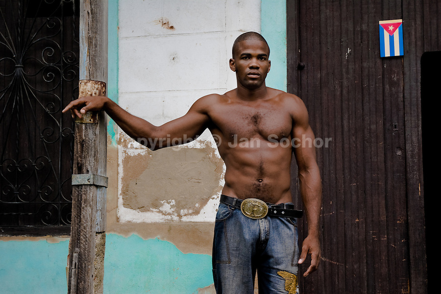 A young Cuban man of an athletic, muscular look stands half naked on the street of Santiago de Cuba, Cuba, 29 July 2008. About 50 years after the national rebellion, led by Fidel Castro, and adopting the communist ideology shortly after the victory, the Caribbean island of Cuba is the only country in Americas having the communist political system. Although the Cuban state-controlled economy has never been developed enough to allow Cubans living in social conditions similar to the US or to Europe, mostly middle-age and older Cubans still support the Castro Brothers' regime and the idea of the Cuban Revolution. Since the 1990s Cuba struggles with chronic economic crisis and mainly young Cubans call for the economic changes.