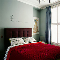 The bedroom is decorated in tones of blue and red. The windows are dressed with simple silk curtains and the bed has an upholstered headboard and a quilted cover
