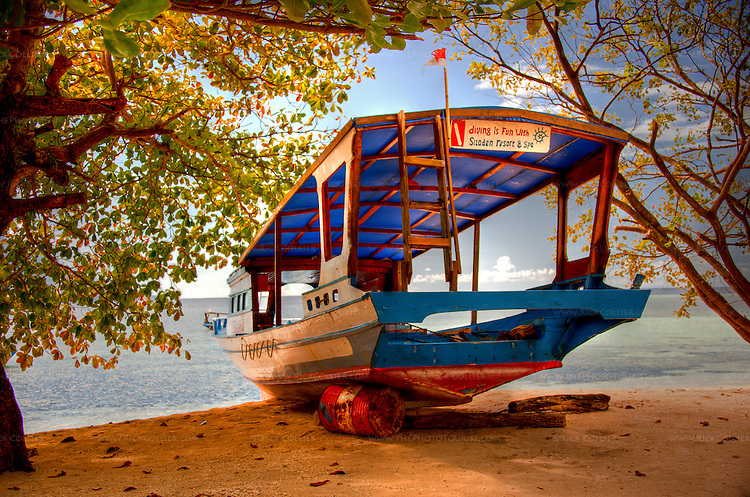 """A dive boat was originally pulled up onto the beach for repair.  Propped upright on the sandy beach near the entrance of the Siladen Resort and Spa, it has become an emblem and landmark for the resort, with the colorful sign """"Diving is Fun at Siladen Resort and Spa.""""  (HDR image, on Siladen Island, Bunaken National Park, North Sulawesi, Indonesia.)"""