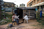 A group of men sit outside a makeshift shop in the in Belgharia township outside of Dhanbad in Jharkhand, India. Families from various villages with underground fires have been rehabilitated in Belgharia township. Photo: Sanjit Das/Panos