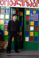 A man stands outside a brightly painted shop in Tbilisi...