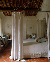Old linen sheets hanging from a metal frame are used as simple but effective curtains for this four-poster bed