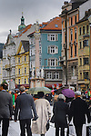 People walking along Maria Theresa street, passing pastel coloured buildings and St Anne's column on arainy day.Innsbruck, Tyrol,Austria.