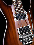 Artistic closeup photo of electric guitar natural brown wood color
