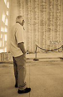 Elderly man viewing the names of those who died during World war II at the Arizona Memorial, Pearl Harbor, Oahu