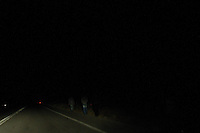 In the early hours of the morning migrants that have just smuggles themselves into Greece walk along the main road in search of the police station. Migrants have been killed by buses whilst walking along the road when dark. Mandra, Evros, Greece.