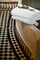 Close up of towels on the edge of a concrete bath and the black and white tiled floor in the bathroom