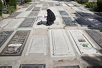 A Iranian woman mourn for his long-time dead relative at the cemetery near the Holy Shrine of Imam Khomeini, Greater Tehran.
