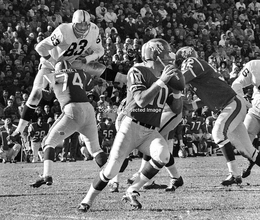 Raiders vs the Denver Broncos, Bronco quarterback Jim LeClair. Raider Ben Davidson is upended. <br />