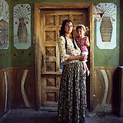 A Roma woman and child stand in front of a painted wall in a house, in the old part of the Sintesti Roma camp.