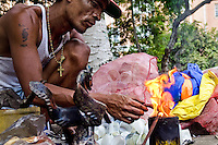 Jhón Jairo Morales, a Colombian street artist, creates a sculpture by melting down used plastic cups on the street of Cali, Colombia, 1 April 2004. Collecting and recycling of used plastic cups from the city dustbins allows him to create simple shaped plastic figures, usually animals. The original sculpture technique is based on melting down plastic in burner fire. Then he shapes fused plastic mechanically and gives the material a design. The artistic process is closed by sinking a figure into the cold water. The artist works and sells his sculptures in the Metropolitan Park of Cali.