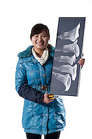 Worker Li Guizhen poses with one of the decorative framed photograph produced in Artissmo Designs factory in Yiwu, Zhejiang province, China, on February 14, 2012. Photo by Lucas Schifres/Pictobank