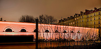 Surrounding wall, Quai Branly Museum, 2007, by architect Jean Nouvel, Paris, France, lit with pink lights and seen from the northern section of the museum featuring tall trees in the foreground. Picture by Manuel Cohen.