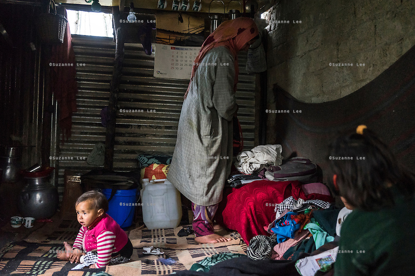 Zainab, 10 months, sits on the floor as her mother, Shugufta, 29, goes about her household chores in her temporary shelter in Narbal village, Jammu and Kashmir, India, on 24th March 2015. When the floods hit in the middle of the night, Shugufta and her family had to walk 5 miles to find shelter. Save the Children supported the family with shelter kits, blankets, hygiene items, food and tarpaulin, which they have used to build a temporary shelter next to their crumbled home. Photo by Suzanne Lee for Save the Children