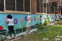 Volunteers touch-up a mural on the side of PS 33 the Chelsea School in the Chelsea neighborhood of New York on Friday, august 1, 2014. (© Richard B. Levine)