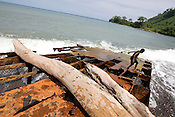 A grounded rusting pontoon barge (used in the logging industry, left by loggers), in the bay of Bain village in the Cape Orford logging concession (run by Rimbunan Hijau- Malaysian logging giants), in Bain, East New Britain Island, Papua New Guinea,  Friday 19th September 2008..