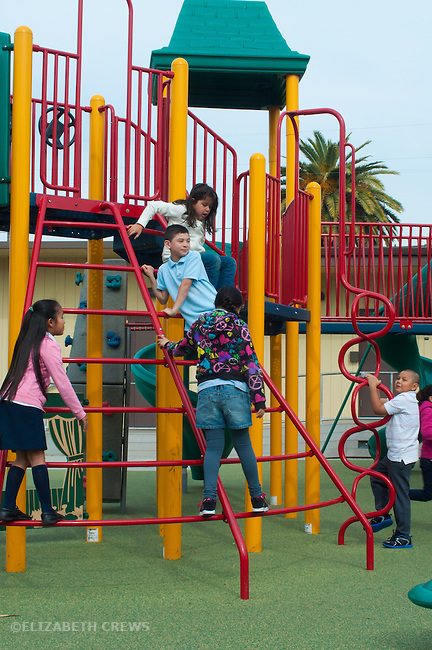 Oakland CA mixed race 2nd 3rd graders playing during recess on new play equipment in inner city school yard