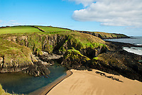 Southwest Ireland Irish coast with sea, blue skies, clouds, sand, green fields, ocean, cove, County Cork