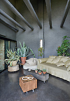 A sitting area in an industrial style space with exposed grey bricks and beams. The room is furnished in a functional style with a sofa and block wood tables on wheels.