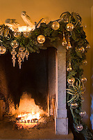 The old stone fireplace has been elaborately decorated with sprigs of spruce and glass baubles