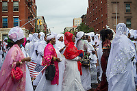 Sengalese immigrants participate in a parade in Harlem in New York commemorating their Shaykh Ahmadou Bamba during the Murid Islamic Community in America (MICA) cultural weeks celebration on Sunday, July 28, 2013. A Murid follows the philosophy of the Sufi Islamic religion and is guided by a murshid, in this case the late Shaykh Ahmadou Bamba who died in 1927. (© Frances M. Roberts)
