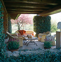 Comfortable cane armchairs and a sofa are grouped around a pair of locally made coffee tables on the covered terrace