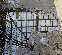Plant History Glasshouse (formerly Australian Glasshouse), 1830s, Rohault de Fleury, Jardin des Plantes, Museum National d'Histoire Naturelle, Paris, France. View from above of a reflection showing the metal and glass roof structure. The pool of water is on paving stones which are classified as Historical Monuments.