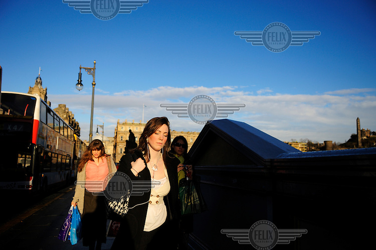 Young women in morning rushhour on North Bridge in Edinburgh city centre.