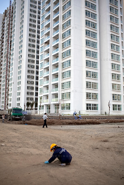 Construction workers sweep up the road in front of the New Saigon building on Nguyen Huu Tho street in District 7 in Ho Chi Minh City, Vietnam...Photo taken Wednesday, November 11, 2009. Kevin German / Luceo Images
