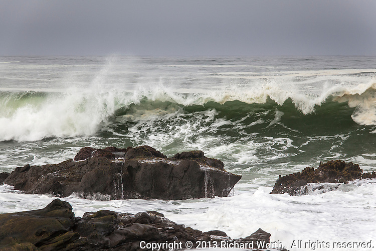 The water glows green under a curling wave at the rocky shore of Bean Hollow State Beach.