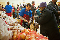 "Volunteers distribute turkeys, stuffing and all the other ""fixin's"" for a Thanksgiving dinner, to the neediest at the Catholic Charities' Lt. Joseph P. Kennedy Center in Harlem in New York on Tuesday, November 22, 2011. The families, who would otherwise not be able to afford the dinner, received the donations during a time where sources of relief for the poor and unemployed are constrained if not terminated. The food is from the generosity of the former baseball player Rusty Staub and the Urso Fund for the Hungry and Homeless. (© Richard B. Levine)."