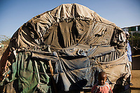 Shelter in State house IDp camp is made from discarded clothes, scraps of fabric, plastic and cardboard stretched over wooden frames. Families as large as 14 share these structures.