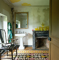 A bathroom in the throes of restoration with unpainted walls and ceiling