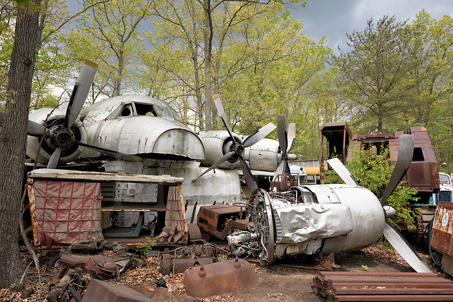 Looks like the old 99-4 is laid up in a salvage boneyard with no parole in sight because those dents and damage are permanent, which means fini. Actually, what appears to be a whole airplane is simply frankensteined together for appearances with the fuselage laid perpendicularly across several other plane bodies, and some engines with props set down in line beside it. There are no wings which have been cut off to transport it here, and not enough room to put four engines up there which leaves one lollygagging on the ground with a bent prop. If you look closely, the fuselage has been split lengthwise with the bottom missing. Here is a good example of owner-initiated impromptu junkyard sculpture...in other words, creative junking!<br /> <br /> This is a mixed salvage yard with all manner of metal collected in amazing piles, old cars and buses, heavy equipment, a few semi-trucks, and lots of airplane parts, a few helicopters, and random military air surplus mixed in throughout. Much of it is piled and stacked up due to the limited acreage. The sheer density of the place can be surprising. Nearly every inch is in use and occupied by something or other, and although the main roads through are clear, getting into and through the nooks and crannies can be a tight fit while carrying shooting equipment. <br /> <br /> So, here lie all the pieces that make up old number 99-4 today, ending its days in an airplane graveyard as an artful arrangement in aluminum done not only for salvage sake, but maybe a little fun too.<br /> <br /> Monthly Newsletter sign up at Dierks Photo on Facebook...