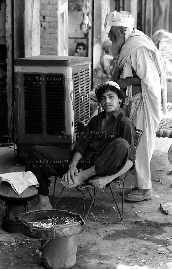 Pakistan 1986 .Darra Adamkhel is Pakistan's largest weapons bazaar and factory, renowned for its gun making expertise since the late 19th century, Darra is a sprawl of hundreds of workshops where some 3,500 gunsmiths toil on replica weapons..A Pakistani tribal man sells bullets